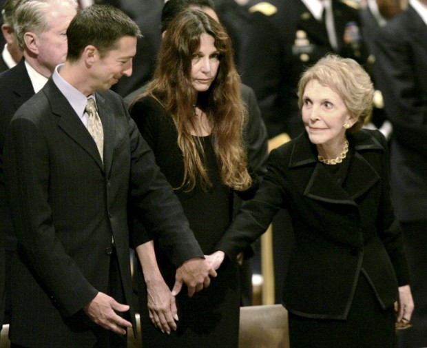 Nancy Reagan (R) reaches out to Ron Reagan Jr., as Patti Davis looks on, during the funeral for former U.S. president Ronald Reagan at the Washington National Cathedral in Washington in this June 11, 2004 file photo. REUTERS/Kevin Lamarque/Files