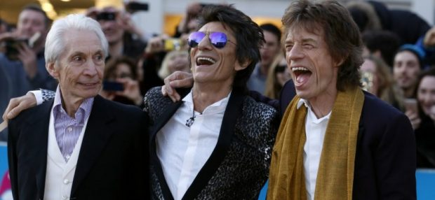 """Members of the Rolling Stones (L-R) Charlie Watts, Ronnie Wood and Mick Jagger laugh as they arrive for the """"Exhibitionism"""" opening night gala at the Saatchi Gallery in London, Britain April 4, 2016. REUTERS/Luke MacGregor"""