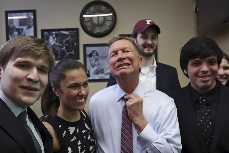 U.S. Republican presidential candidate John Kasich adjusts his tie as he poses for a photo with supporters before a meet and greet at the Arthur Avenue Market in the Bronx borough of New York