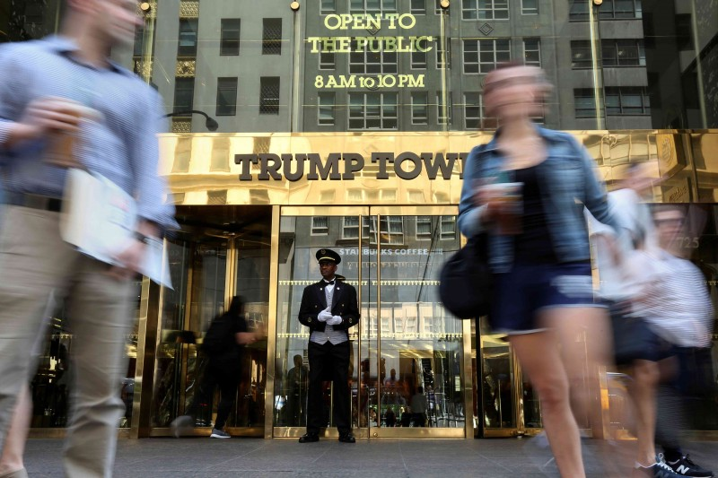 A doorman stands as people walk past the Trump Tower in New York (Reuters Pictures)