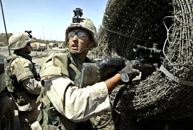 U.S. Captain Jesus Salas of the 1st Cavalry Division carries a roll of barbed wire in Baghdad's Shi'ite suburb al-Sadr City August 18, 2004. REUTERS/Pool/David P. Gilkey
