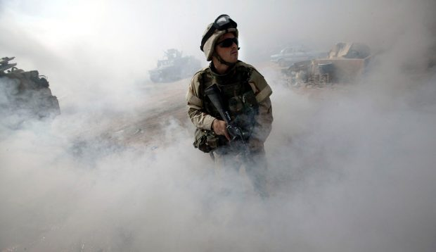 Specialist Jeffrey Ward, of Arlington, Virginia, a medic with the U.S. Army's 1st Cavalry Division, 1st Brigade, 1-12 Cav, stands guard in a haze of smoke outside a building during a cordon and search operation in a neighbourhood near the Baghdad suburb of al Sadr City August 15, 2004. Insurgents fired mortars at a meeting where Iraqi leaders met to pick an interim national assembly Sunday, killing at least two people in a grim reminder of the country's tortured path toward democracy. REUTERS/David P. Gilkey/Detroit Free Press/Knight Ridder-Pool