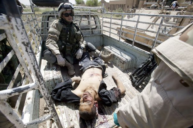 BAGHDAD, IRAQ - AUGUST 14: Spec. Jeffrey Ward, a medic with the U.S. Armys 1st Cav, 1st Brigade, 112 Cav. from Fort Hood Texas, sits in the back of a pickup after trying to save a Iraqi man who was shot August 14, 2004 in Baghdad, Iraq. The man's family was trying to transport him to a hosiptal after being wounded in clashes in a neighborhood outside of Sadr City. He died despite medical efforts by the soldiers. (Photo by David P. Gilkey-Pool/Getty Images)