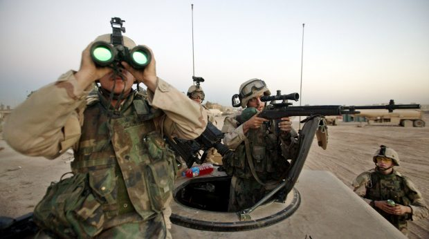 U.S. Army's 1st Cavalry Division sniper Aaron McAlister, from Maypearl Texas (L) and his counterpart Chuck Ayars, from Nashville Tennessee (C) take aim at a suspected enemy observer at Camp Eagle, outside the eastern Baghdad's Shi'ite suburb of al-Sadr City August 16, 2004. Fresh fighting between U.S. forces and Sadr's Mehdi militia broke out in a Shi'ite slum in Baghdad, witnesses said. They said U.S. troops were sealing off the area, called Sadr City. REUTERS/Pool/David P. Gilkey