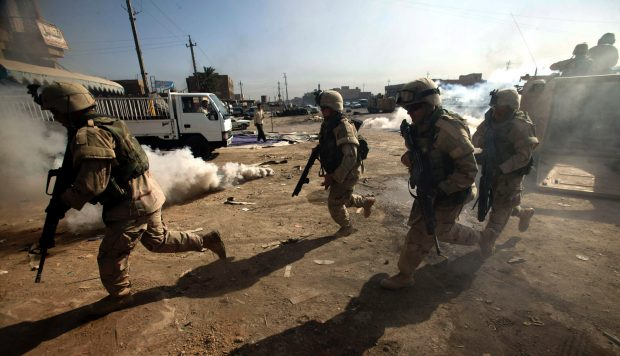 U.S. Army troops from the U.S. Army's 1st Cavalry Division, 1st Brigade, 1-12 Cav run into a building during a cordon and search operation in a neighbourhood near the Baghdad suburb of al Sadr City August 15, 2004. Insurgents fired mortars at a meeting where Iraqi leaders met to pick an interim national assembly Sunday, killing at least two people in a grim reminder of the country's tortured path toward democracy. REUTERS/David P. Gilkey/Detroit Free Press/Knight Ridder-Pool