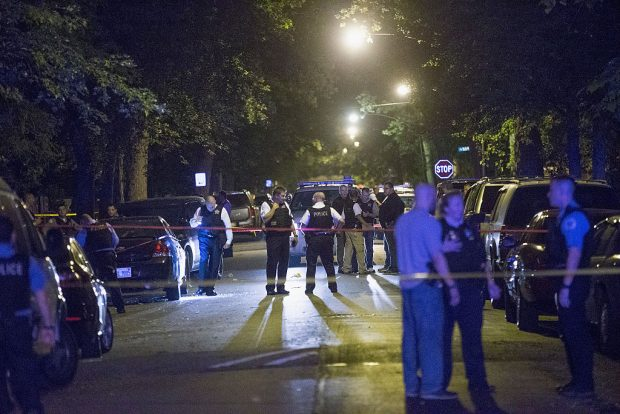 CHICAGO, IL - SEPTEMBER 28: Police officers investigate a shooting scene where 5 people were reported to have been shot, including an 11-month-old infant, on September 28, 2015 in Chicago, Illinois. Chicago, like many major cities in the United States, has experienced a surge in shootings this year. (Photo by Scott Olson/Getty Images)