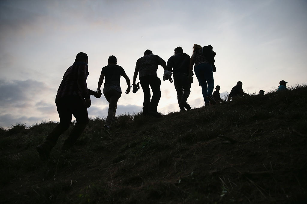 Undocumented immigrants are led after being caught and handcuffed by Border Patrol agents near the U.S.-Mexico border (Getty Images)