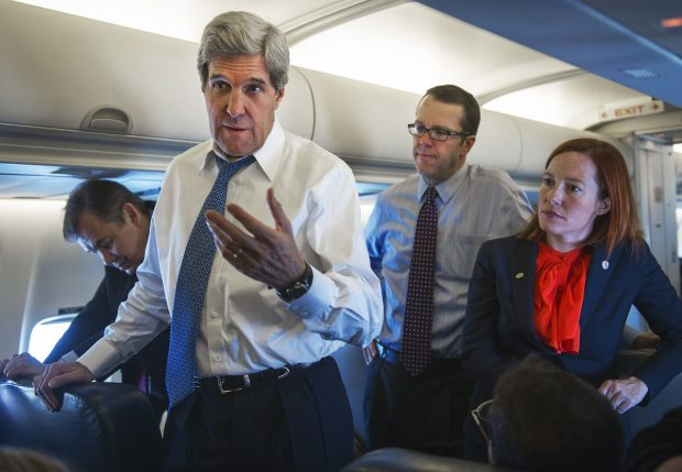 Jen Psaki stands behind Secretary of State John Kerry as he talks with reporters aboard his government aircraft shortly after departing Seoul Air Base April 13, 2013, for Beijing, China