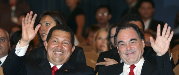 "Venezuela's President Chavez and U.S. director Stone wave as they sit during the ""South Of The Border "" premiere at the 66th Venice Film Festival"