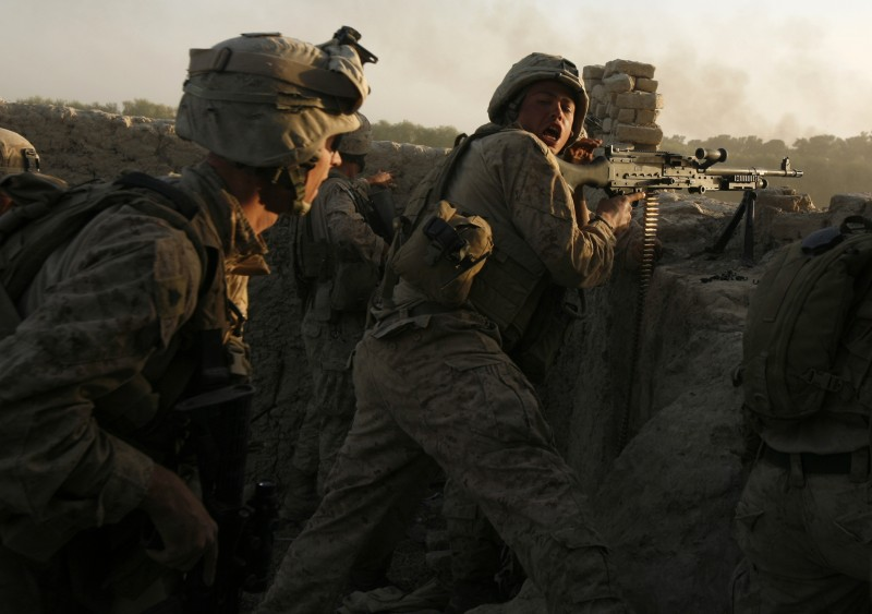U.S. marines fire during a Taliban ambush as they carry out an operation to clear an area in Helmand province, October 2009. REUTERS/Asmaa Waguih