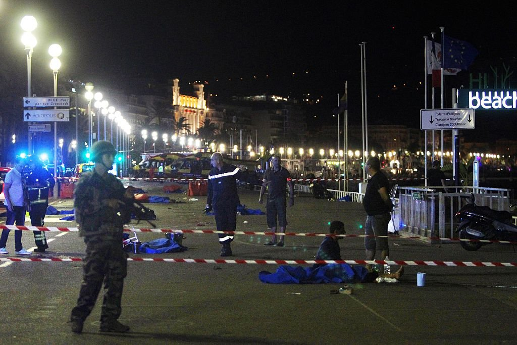 Soldiers, police officers and firefighters walk near dead bodies covered with a blue sheets on the Promenade des Anglais seafront in the French Riviera town of Nice (Getty Images)