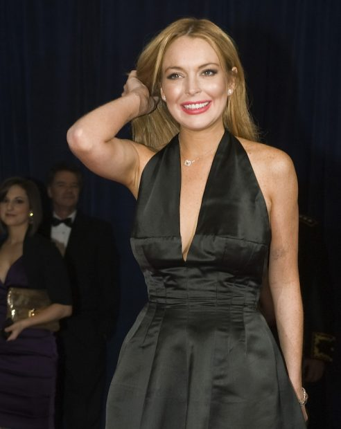 Actress Lindsay Lohan fixes her hair on the red carpet as she arrives for the annual White House Correspondents' Association Dinner at the Washington Hilton in Washington April 28, 2012. REUTERS/Jonathan Ernst (UNITED STATES - Tags: POLITICS ENTERTAINMENT) - RTR31D30