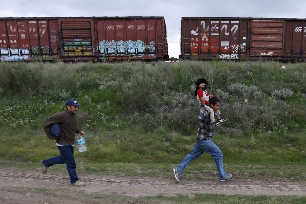A Salvadoran father (R) carries his son while running next to another immigrant as they try to board a train heading to the Mexican-U.S. border, in Huehuetoca, near of Mexico City, June 1, 2015. An increasing number of Central Americans are sneaking across Mexico's border en route to the United States. Picture taken June 1, 2015. REUTERS/Edgard Garrido - RTR4YKNV