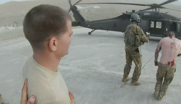 SSG. Glassford waits behind Sgt. Grasso, whose lower back bares open wounds (photo: via Spc. Morgan's helmet cam)
