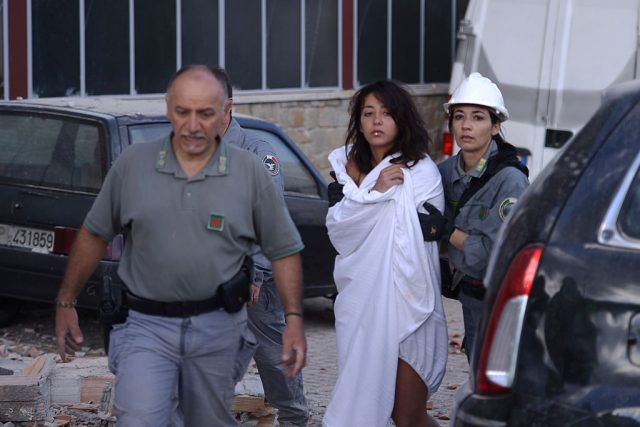 Rescuers help a woman among damaged buildings after a strong earthquake hit central Italy, in Amatrice on August 24, 2016. A powerful 6.2-magnitude earthquake devastated mountain villages in central Italy on Wednesday, leaving at least 18 people dead and dozens more injured or unaccounted for. Scores of buildings were reduced to dusty piles of masonry in communities close to the epicentre of the pre-dawn quake in a remote area straddling the regions of Umbria, Marche and Lazio. (Photo: FILIPPO MONTEFORTE/AFP/Getty Images)
