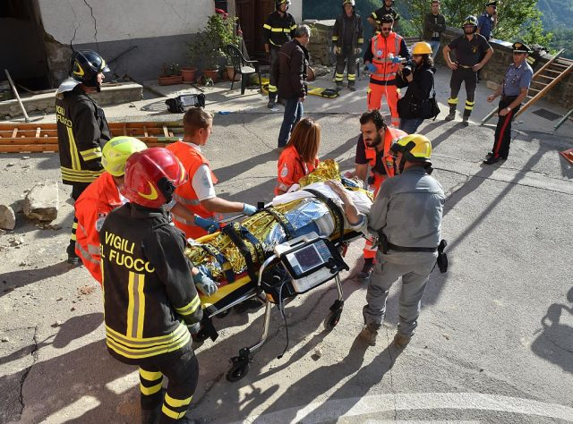 Rescuers carry a man on a stretcher after a strong earthquake hit central Italy, in Arquata del Tronto on August 24, 2016. A powerful 6.2-magnitude earthquake devastated mountain villages in central Italy on August 24, 2016, leaving at least 18 people dead and dozens more injured or unaccounted for. Scores of buildings were reduced to dusty piles of masonry in communities close to the epicentre of the pre-dawn quake in a remote area straddling the regions of Umbria, Marche and Lazio. (Photo: FILIPPO MONTEFORTE/AFP/Getty Images)