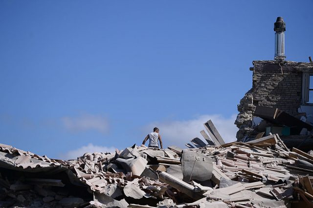 A man sits on top of rubble in Amatrice on August 24, 2016 after a powerful earthquake rocked central Italy. The earthquake left 38 people dead and the total is likely to rise, the country's civil protection unit said in the first official death toll. Scores of buildings were reduced to dusty piles of masonry in communities close to the epicentre of the pre-dawn quake in a remote area straddling the regions of Umbria, Marche and Lazio. (Photo: FILIPPO MONTEFORTE/AFP/Getty Images)