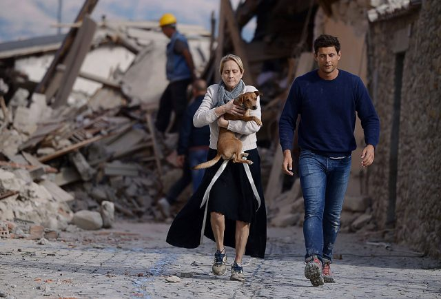 A woman holds a dog in her arms as she walks with a man next to the rubble of buildings in Amatrice on August 24, 2016 after a powerful earthquake rocked central Italy. The earthquake left 38 people dead and the total is likely to rise, the country's civil protection unit said in the first official death toll. Scores of buildings were reduced to dusty piles of masonry in communities close to the epicentre of the pre-dawn quake in a remote area straddling the regions of Umbria, Marche and Lazio. (Photo: FILIPPO MONTEFORTE/AFP/Getty Images)