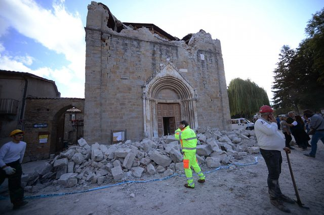 People stand in front of a damaged church in Amatrice on August 24, 2016 after a powerful earthquake rocked central Italy. The earthquake left 38 people dead and the total is likely to rise, the country's civil protection unit said in the first official death toll. Scores of buildings were reduced to dusty piles of masonry in communities close to the epicentre of the quake, which had a magnitude of between 6.0 and 6.2, according to monitors. (Photo: FILIPPO MONTEFORTE/AFP/Getty Images)