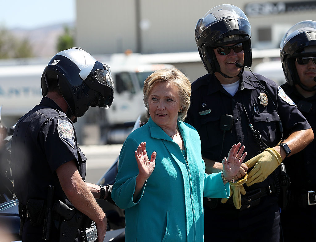 Hillary Clinton talks with Reno police officers before getting onto her plane at Reno Tahoe International Airport (Getty Images)