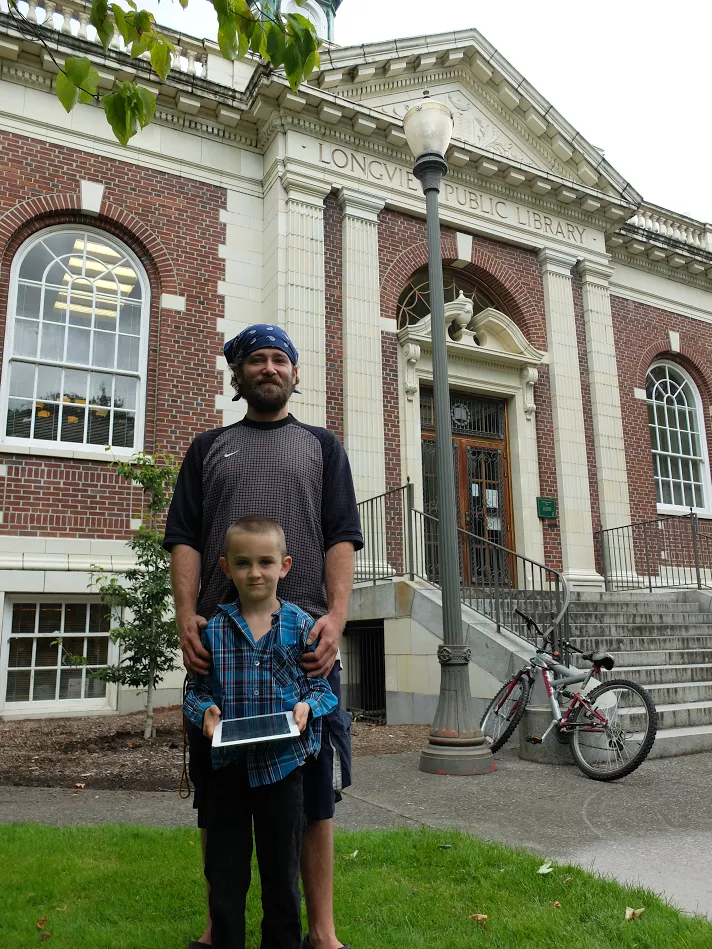 Eric Gray and his son stand in front of the Longview Public Library. (Joseph Hammond/TheDCNF)