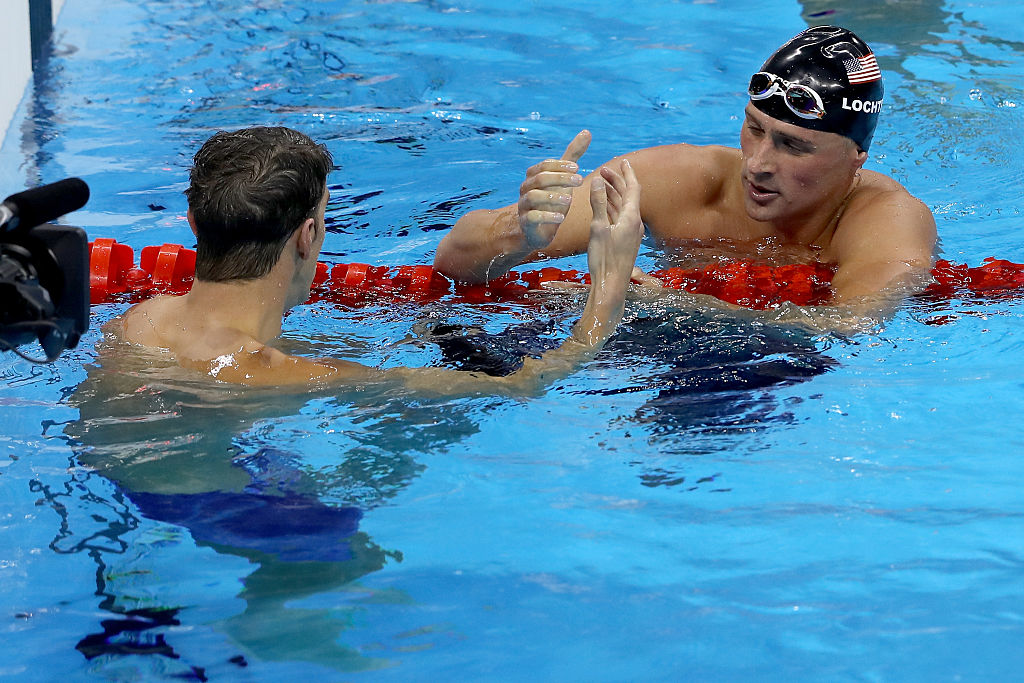 RIO DE JANEIRO, BRAZIL - AUGUST 11: Michael Phelps of the United States shakes hands with Ryan Lochte of the United States after winning the Men's 200m Individual Medley Final on Day 6 of the Rio 2016 Olympic Games at the Olympic Aquatics Stadium on August 11, 2016 in Rio de Janeiro, Brazil. (Photo by Al Bello/Getty Images)