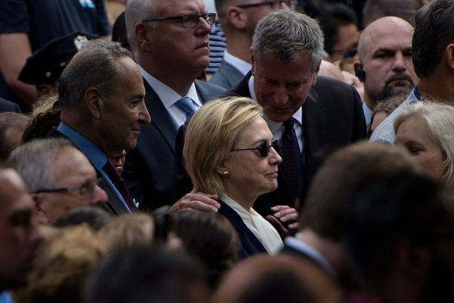 New York City Mayor Bill de Blasio speaks to Democratic presidential nominee Hillary Clinton during a memorial service at the National 9/11 Memorial September 11, 2016 in New York.