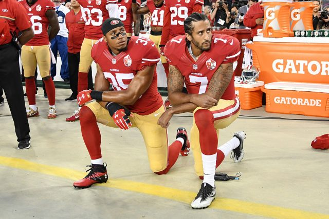 Colin Kaepernick #7 and Eric Reid #35 of the San Francisco 49ers kneel in protest during the national anthem prior to playing the Los Angeles Rams in their NFL game at Levi's Stadium on September 12, 2016 in Santa Clara, California
