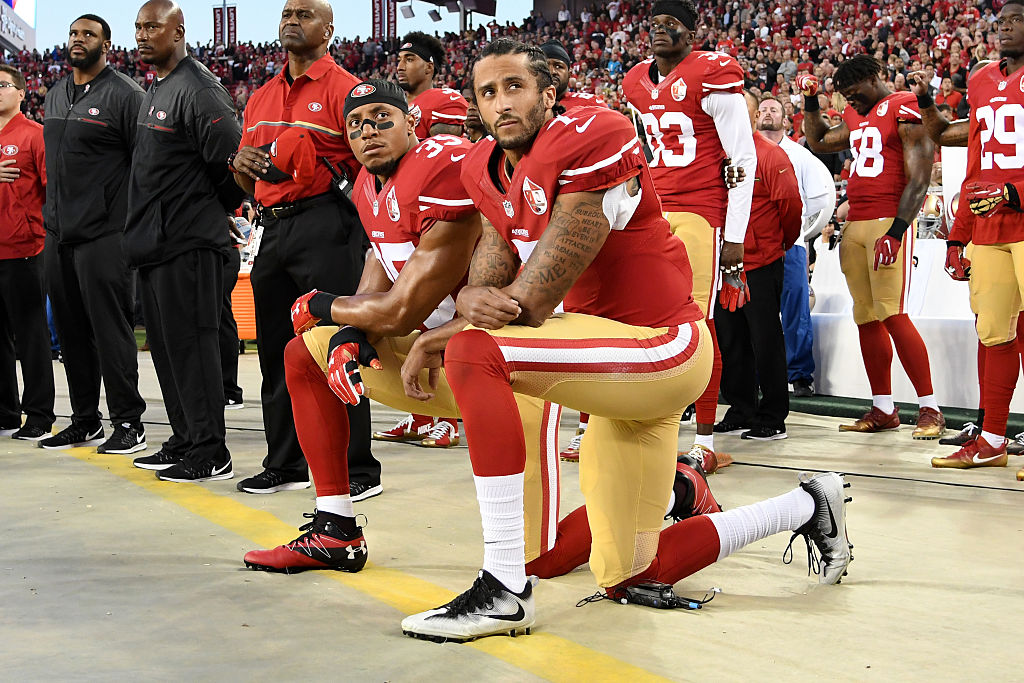 Colin Kaepernick and Eric Reid kneel during the national anthem Monday night in San Francisco. (Photo credit: Getty Images)
