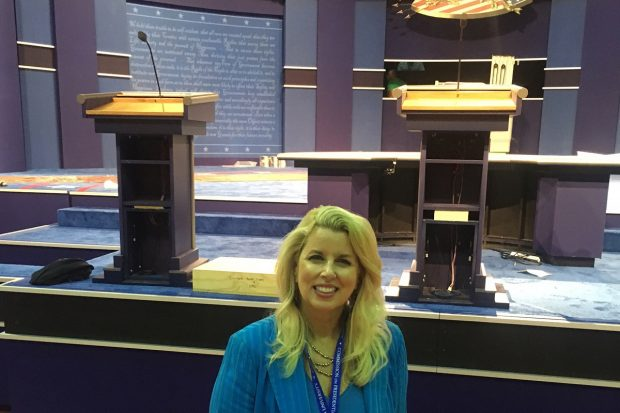 Rita Cosby pictured with two presidential debate podiums at Hofstra University in Hempstead, NY. Podium on the right has plywood in it to heighten it, likely for Secretary Clinton. Photo: Rita Cosby/WABC Radio