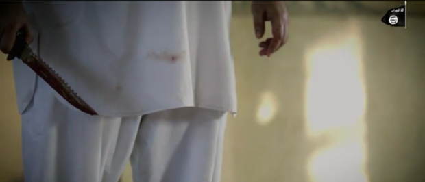 An ISIS executioner holds a bloody knife after slaughtering a prisoner. Source: Video Screengrab