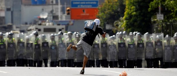 A protester throws a stone while taking part in a rally to demand a referendum to remove Venezuela's President Nicolas Maduro in Caracas