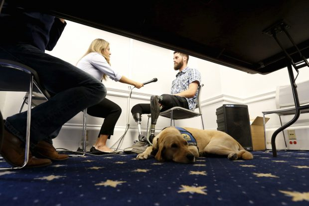 Knoxville, a trained service dog, lies at the feet of LeRoy after a U.S. House Military Veterans Caucus briefing on legislation promoting service dogs for military veterans on Capitol Hill in Washington