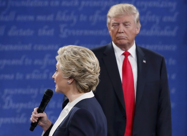 Democratic U.S. presidential nominee Hillary Clinton speak as Republican U.S. presidential nominee Donald Trump looks on during their presidential town hall debate at Washington University in St. Louis, Missouri, U.S., October 9, 2016. REUTERS/Jim Young