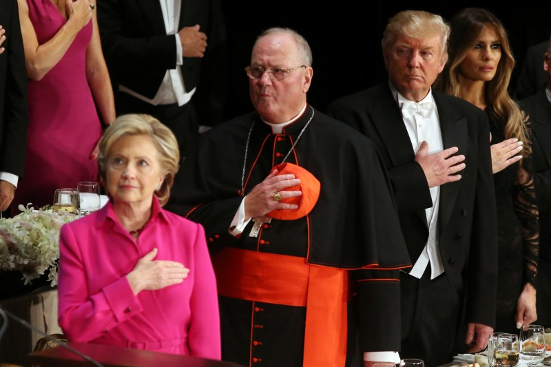 Donald Trump looks at Hillary Clinton during the national anthem as they attend the Alfred E. Smith Memorial Foundation dinner to benefit Catholic charities in New York. REUTERS/Carlos Barria
