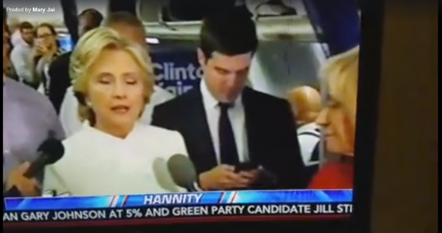 Clinton spokesman Nick Merrill typing on his phone before showing it to Andrea Mitchell. [YouTube screengrab/https://www.youtube.com/watch?v=KYfdc36HnHo&sns=tw]