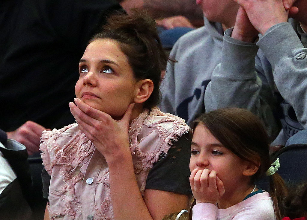 Actress Katie Holmes and her daughter Suri Cruise attend a NCAA basketball game in New York City. (Photo by Elsa/Getty Images)