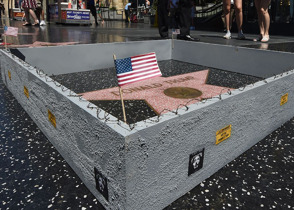 The Hollywood Walk of Fame Star of Republican presidential candidate Donald Trump is surrounded by a miniture barbed-wire wall placed there by Californian street artist Plastic Jesus in Hollywood, California. (Photo credit: MARK RALSTON/AFP/Getty Images)