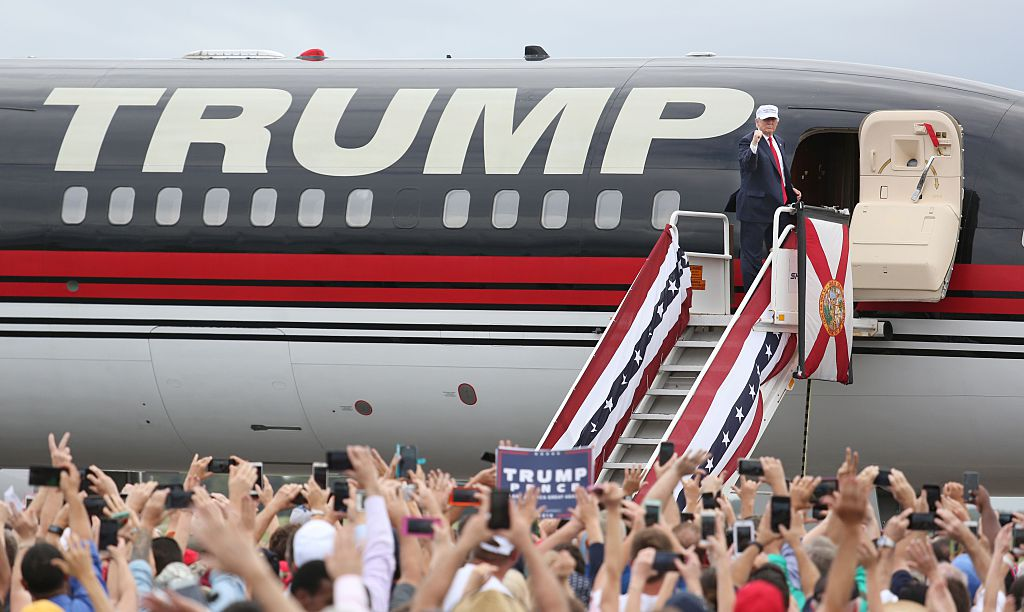 Republican presidential nominee Donald Trump pumps his fist to supporters at the conclusion of his campaign event on the tarmac at Lakeland Linder Regional Airport in Lakeland, Florida (Photo credit: Gregg Newton/AFP/Getty Images)