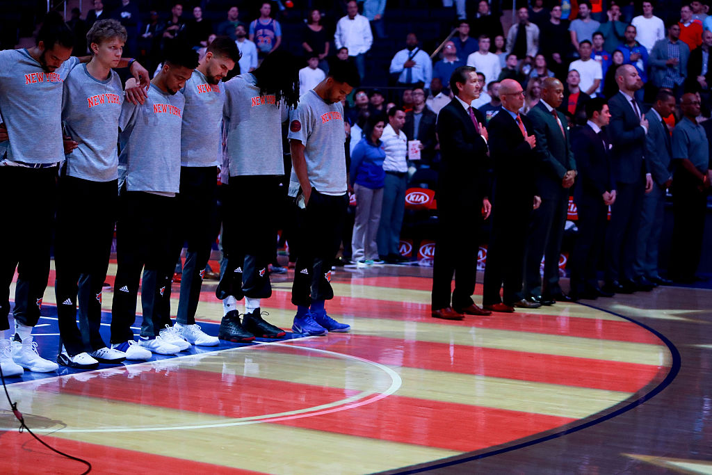 The New York Knicks pause for the national anthem prior to the their preseason game against the Boston Celtics at Madison Square Garden. (Photo by Michael Reaves/Getty Images)