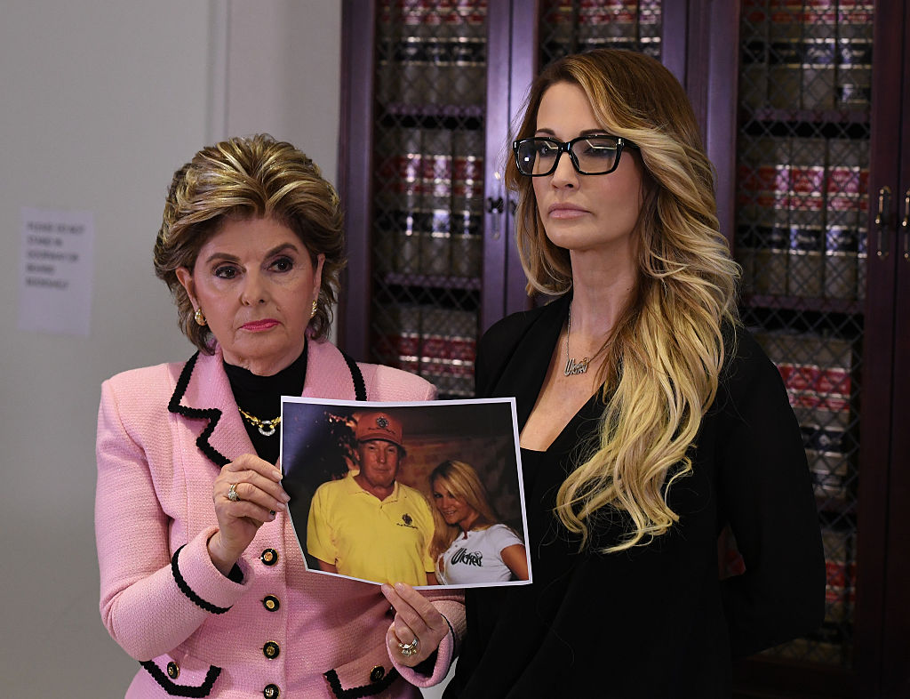 Adult film star Jessica Drake stands with a photo of her meeting with Donald Trump, beside attorney Gloria Allred as they talk about allegations of sexual misconduct against the Republican presidential hopeful during a press conference in Los Angeles on October 22, 2016. (Photo credit: MARK Ralston/AFP/Getty Images)