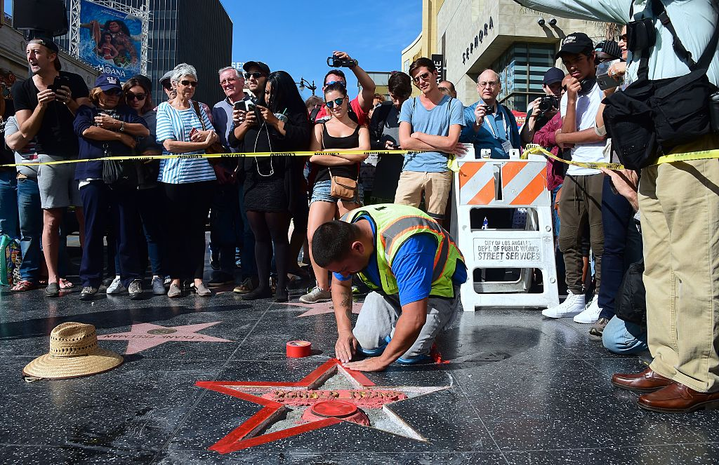 A crowd gathers to watch as Donald Trump's vandalized Star is tended to and cleaned up before being replaced. (Photo credit: FREDERIC J. BROWN/AFP/Getty Images)