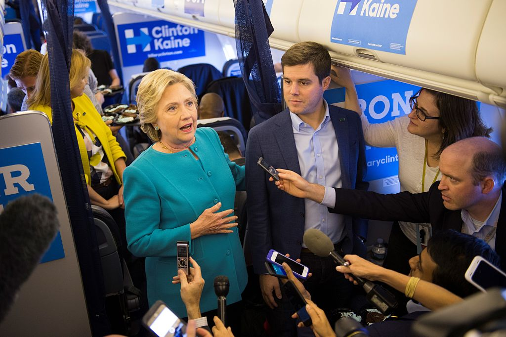 Hillary Clinton stands beside staff member Nick Merrill and takes questions from the traveling press on her plane while en-route from Tampa, Florida to Laguardia Airport in New York on October 26, 2016. (Getty Images)
