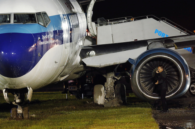 A man speaks on his phone after inspecting a campaign plane that had been carrying U.S. Republican vice presidential nominee Mike Pence after it skidded off the runway while landing in the rain at LaGuardia Airport in New York, October 27, 2016
