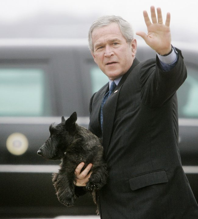 President George W. Bush carries his pet dog, Barney, after arriving on Air Force One at Andrews Air Force Base outside Washington from his Central Texas ranch in Crawford January 1, 2007. REUTERS/Larry Downing