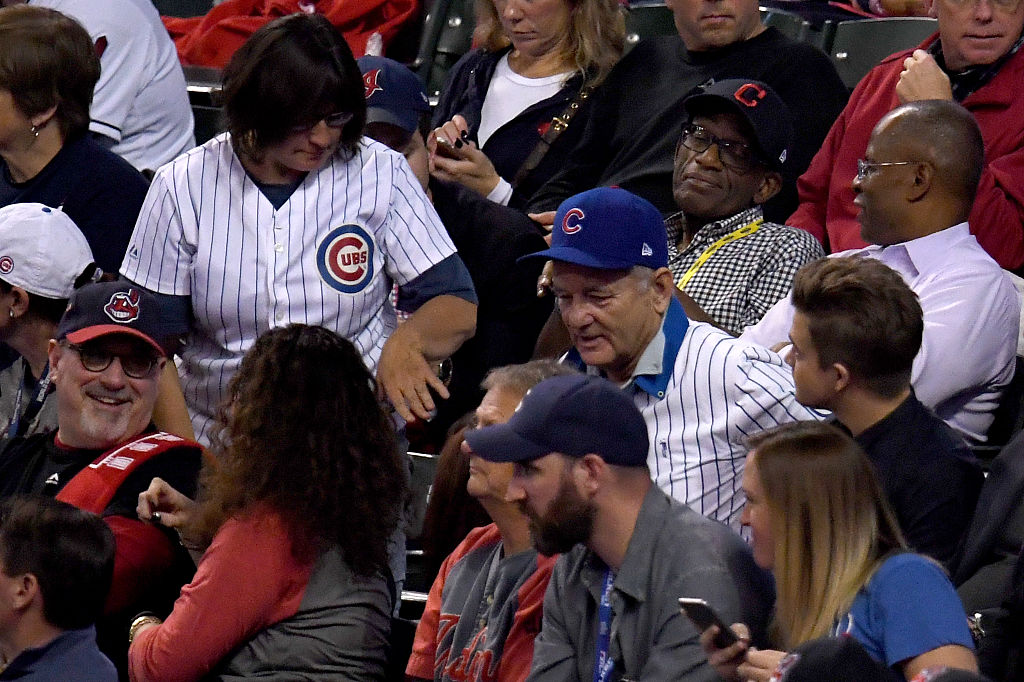 Michel shuffles into her seat next to Bill Murray at Game Six of the 2016 World Series. (Photo by Jason Miller/Getty Images)