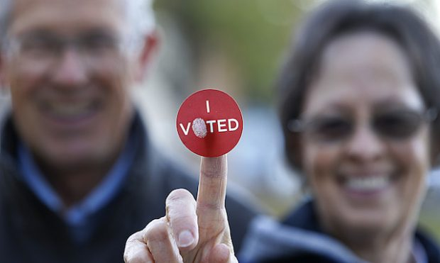 """A couple shows off their """"I Voted"""" sticker as they leave Wasatch Elementary school after casting their ballot in the presidential election on November 8, 2016 in Provo, Utah. (Photo by George Frey/Getty Images)"""