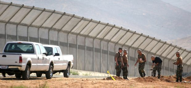 Members of the U.S. National Guard work along a new border fence near the U.S.-Mexico border in Otay Mesa, San Diego July 21, 2006. (REUTERS/Jorge Duenes)