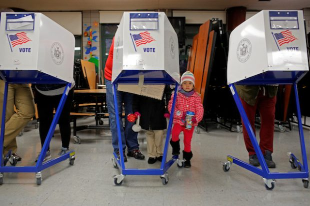Myla Gibson, 3, waits as her father Ken Gibson fills out a ballot for the U.S presidential election at the James Weldon Johnson school in the East Harlem neighbourhood of Manhattan, New York City, U.S. November 8, 2016. REUTERS/Andrew Kelly