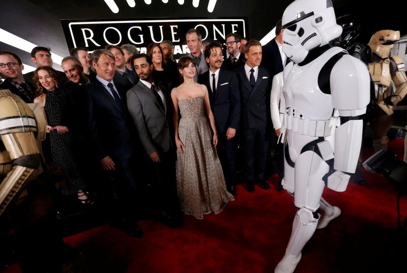 """The cast and crew pose on the red carpet while a """"Storm Trooper"""" walks by as they arrive at the world premiere of the film """"Rogue One: A Star Wars Story"""" in Hollywood, California, U.S., December 10, 2016. REUTERS/Mario Anzuoni TPX IMAGES OF THE DAY"""